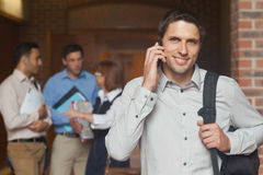 Cheerful attractive mature student phoning in corridor Stock Photo