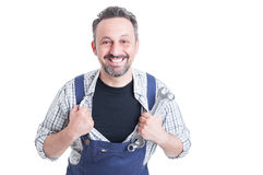 Cheerful attractive mechanic with metallic spanner acting like s Stock Photography