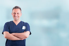 Cheerful attractive medic standing with folded arms and posing. Against blue background with copyspace Stock Image