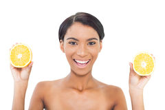Cheerful attractive model holding slices of orange in both hands Stock Photo