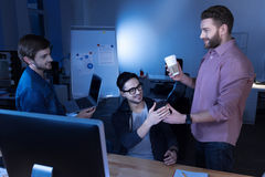 Cheerful attractive programmers enjoying their break. Break from work. Cheerful attractive male programmers looking at each other and smiling while having a Stock Image