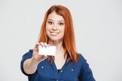 Cheerful attractive redhead young woman showing blank card Stock Images