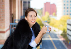 A cheerful, attractive, rich  businesswoman holding coffee mug Stock Image
