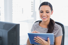 Cheerful attractive secretary scrolling on tablet pc. In her office Stock Photos