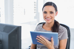 Cheerful attractive secretary using tablet pc Stock Photos