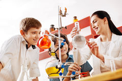 Cheerful attractive teacher showing a chemical flask Stock Photo