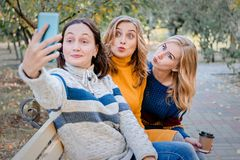Cheerful attractive three young women best friends having fun together outside and making selfie. royalty free stock photography