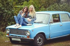 Cheerful Attractive two young blonde girl and brunette posing on the hood of an old rusty car, dressed in jeans and shirts on a na. Ture background stock images