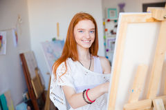 Cheerful attractive woman artist painting on canvas in art workshop. Cheerful attractive young woman artist with red hair painting on canvas in art workshop royalty free stock photos