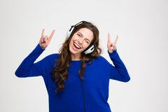 Cheerful attractive woman in earphones listening to music and winking Royalty Free Stock Image