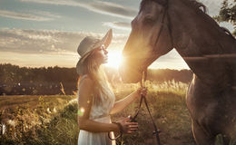 Cheerful, attractive woman with a majestic horse Royalty Free Stock Photography