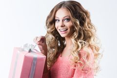 Cheerful attractive woman with opening gift on white. Cheerful attractive woman with opening gift on white background Stock Image