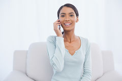 Cheerful attractive woman on the phone sitting on cosy sofa Stock Photo