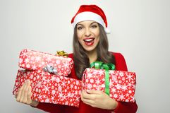 Cheerful attractive woman smiling with Santa Claus hat holding christmas presents on white background royalty free stock images
