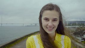 Cheerful attractive woman in yellow dress standing at the embankment stock footage