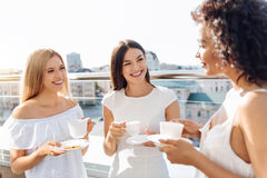 Cheerful attractive women having tea together. Meeting friends. Cheerful attractive delighted women standing together on the rooftop and talking to each other Royalty Free Stock Images