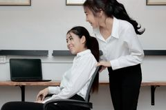 Cheerful attractive young Asian business women push chair and having fun together in office. Cheerful attractive young Asian business women push chair and Royalty Free Stock Photography