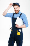 Cheerful attractive young builder in overall and cap holding laptop Stock Image