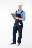 Cheerful attractive young builder standing and writing on clipboard Stock Photography