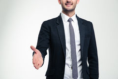 Cheerful attractive young businessman giving hand for handshake Royalty Free Stock Photos