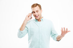 Cheerful attractive young businessman standing and talking on cell phone Stock Photos