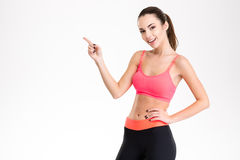 Cheerful attractive young fitness woman pointing away Stock Images