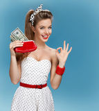 Cheerful attractive young lady holding cash and showing It's Okay. Shopping concept Royalty Free Stock Photo