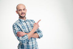 Cheerful attractive young man in plaid shirt pointing away Royalty Free Stock Images