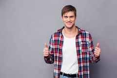 Cheerful attractive young man in plaid shirt showing thumbs up Royalty Free Stock Images
