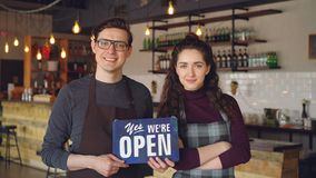 Cheerful attractive people coffee-house owners are holding `we are open` sign while standing inside coffee shop. Opening stock footage