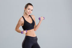 Cheerful attractive young sportswoman lifting dumbbells Stock Image