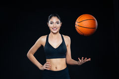Cheerful attractive young sportswoman throwing up orange basketball ball Stock Photos