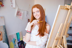 Cheerful attractive young woman artist painter sketches by pencil Royalty Free Stock Image