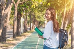 Cheerful attractive young woman with backpack and notebook and standing in the park stock photography