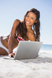 Cheerful attractive young woman in bikini with her laptop Stock Image