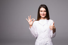 Cheerful attractive young woman doctor holding a pill and showing thumbs up over grey background. Royalty Free Stock Photos