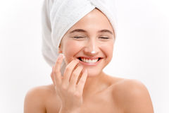 Cheerful attractive young woman with face cream on her nose Royalty Free Stock Photos
