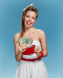 Cheerful attractive young woman holding money and happy smiling. Shopping concept Stock Image