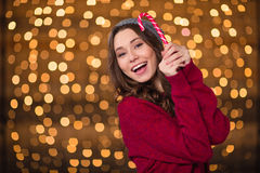 Cheerful attractive young woman holding sweet candy cane and smiling Royalty Free Stock Images
