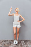 Cheerful attractive young woman standing and pointing up. Over gray background Royalty Free Stock Photography