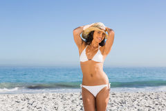 Cheerful attractive young woman wearing straw hat posing. On the beach Stock Photos