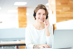 Cheerful attractive young woman working with headset and laptop Royalty Free Stock Image