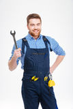 Cheerful attractive young worker in overall holding wrench. Isolated Royalty Free Stock Images