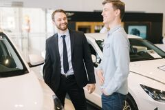 Free Cheerful Automobile Seller Wearing Business Suit Is Having Conversation With Handsome Rich Young Man Stock Photos - 186313413