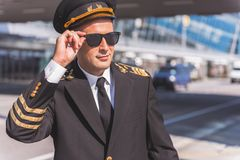 Confident pilot wearing special uniform. Cheerful aviator in sunglasses is looking aside with light smile. He standing outside near airport building . Waist up Stock Images