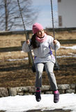 Cheerful babe swinging on the swing in the playground Stock Images