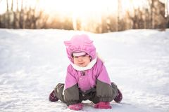 Cheerful baby on all fours playing on snow in cold sunny winter day  in warm clothes  with sunlight through trees. Cute baby on all fours playing on snow in cold Stock Photo