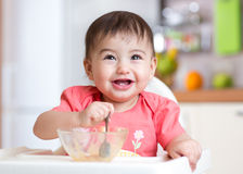 Cheerful baby child eating food itself with a spoon Stock Images