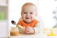 Cheerful baby child eats food itself with spoon. Portrait of happy kid boy in high-chair. Cheerful baby child eats food itself with spoon. Portrait of happy kid stock photo