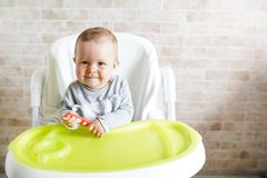 Cheerful baby child eats food itself with spoon. Portrait of happy kid in high chair in sunny kitchen. background with copy space.  royalty free stock images